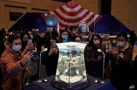 Visitors to the National Museum look at a display of the lunar rock samples retrieved from the moon by China's Chang'e 5 lunar lander late last year in Beijing, March 12, 2021.