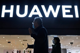 Residents wearing face masks pass by a Huawei electronics store in Beijing on Monday, April 12, 2021. Embattled Chinese tech…