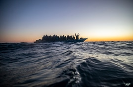 FILE - Migrants and refugees from various African countries aboard a wooden boat in the Mediterranean Sea.