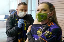 Stephanie Birman, right, a Seattle Sounders season ticket holder, gets vaccinated for COVID-19.