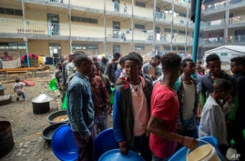 Displaced Tigrayans queue to receive food at the Hadnet General Secondary School which has become a makeshift home to thousands…