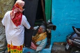 An Indian health worker checks body temperature of a woman during a door-to-door survey being conducted as a precaution against…