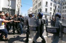 Demonstrators face police officers in Algiers, Friday, May 7, 2021 as a crowd of protesters marched in the streets of Algeria's…