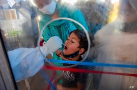 A health worker takes a mouth swab sample of a Kashmiri boy to test for COVID-19 in Srinagar, Indian controlled Kashmir,…