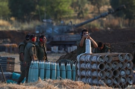 Israeli soldier arms artillery shells next to an artillery unit at the Israeli Gaza border, May 13, 2021.