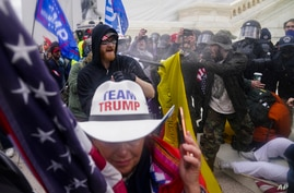 Rioters try to break through a police barrier, at the Capitol in Washington, Jan. 6, 2021.