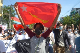 Anti-coup protesters display a party flag of the National League for Democracy (NLD) during a demonstration in Yangon, Myanmar,…