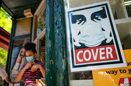 A customer exits a corner market while wearing a protective mask in the retail shopping district of the SoHo neighborhood of…