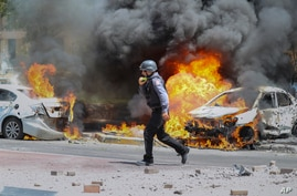 An Israeli firefighter walks next to cars hit by a missile fired from Gaza Strip, in the southern Israeli town of Ashkelon.