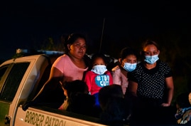 Migrants from Honduras wait in a Border Patrol truck after turning themselves in upon crossing the U.S.-Mexico border Monday,…