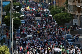 Palestinians living in Lebanon hold placards and Palestinian flags during a march in support of Palestinians, in Beirut, Lebanon, May. 18, 2021.
