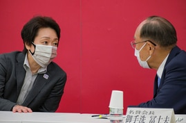 President of the Tokyo 2020 Organizing Committee of the Olympic and Paralympic Games Seiko Hashimoto, left, talks with Canon…
