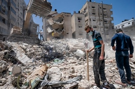 Heavy construction equipment is used to sift through rubble of a building destroyed in Israeli an airstrike on in Gaza City prior to a cease-fire that halted an 11-day war between Gaza and Israel, May 27, 2021.