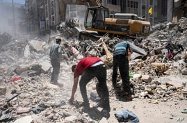 Heavy construction equipment is used to sift through rubble to uncover valuables before it is transported away from the scene of a building destroyed in an airstrike prior to a cease-fire that halted an 11-day war between Gaza's Hamas rulers and Israel, Thursday, May 27, 2021, in Gaza City. (AP Photo/John Minchillo)