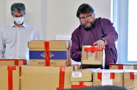 FILE— In this Tuesday May 11, 2021 file photo, election auditors Harri Hursti, right, and Mark Lindeman, catalog ballot boxes…