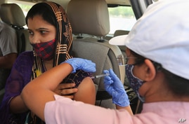A woman receives a dose of Covishield, the Oxford-AstraZeneca vaccine for COVID-19 in her car at a drive-in vaccination facility in Ahmedabad, India, May 28, 2021.