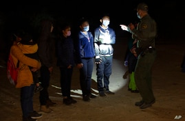 FILE - In this March 28, 2021 file photo Migrants from Guatemala and Honduras are questioned by a Border Patrol agent after…