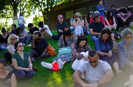 People bow their heads in prayer at a memorial for the lives lost during centennial commemorations of the Tulsa Race Massacre,…