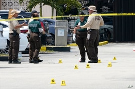 Law enforcement officials work the scene of a shooting outside a banquet hall near Hialeah, Fla., Sunday, May 30, 2021. Two…