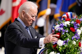 President Joe Biden adjusts a the wreath at the Tomb of the Unknown Soldier at Arlington National Cemetery on Memorial Day.