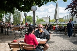 A guest enjoys his beer at a beer garden near the Chancellery in Berlin, Germany, May 21, 2021, as parts of the country began easing COVID-19 restrictions.