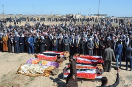 FILE - Iraqi mourners pray at the funeral of eight people killed a day earlier in attacks claimed by the Islamic State (IS) group, in the al-Bou Dor village of the Salaheddin governorate north of the capital, March 13, 2021.