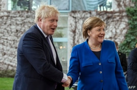 FILE - German Chancellor Angela Merkel, right, greets Britain's Prime Minister Boris Johnson upon his arrival for a meeting at the Chancellery in Berlin, Jan. 19, 2020.