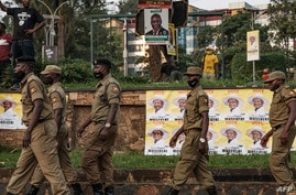 FILE - Security service members wait for the arrival of Ugandan President Yoweri Museveni on his way back from his country home, in Kampala, Uganda, Jan. 21, 2021.