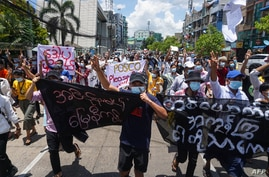 Protesters hold banners as they make the three-finger salute during a demonstration against the military coup in Yangon, Myanmar, May 12, 2021.