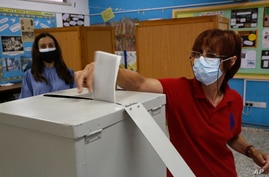 A woman wearing a protective mask casts her vote at a polling station during parliamentary elections, in Deftera, a suburb of capital Nicosia, Cyprus, May 30, 2021.