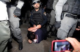 An Israeli police officer restrains a Palestinian during a protest ahead of a court verdict that may forcibly evict Palestinian families from their homes, in the Sheikh Jarrah neighborhood of East Jerusalem, May 5, 2021.