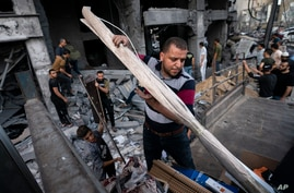 People salvage items from inside the severely damaged Al-Jawhara building following a cease-fire reached after an 11-day war between Gaza's Hamas rulers and Israel, in Gaza City, May 21, 2021.