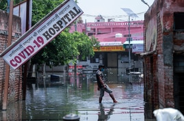 A man wades through water after heavy rains flooded the premises of a COVID-19 hospital being set up at Ghaziabad, on the outskirts of New Delhi, India, May 23, 2021.