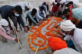 Family members and relatives pray after burying a person who died of reasons other than COVID-19 in a shallow sand grave on the banks of river Ganges in Prayagraj, India, May 16, 2021.