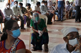 People wait to receive a COVID-19 vaccine outside an inoculation site in Mumbai, India, May 13, 2021.