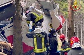 Rescuers work by the wreckage of a cable car after it collapsed near the summit of the Stresa-Mottarone line in the Piedmont region, northern Italy, May 23, 2021.