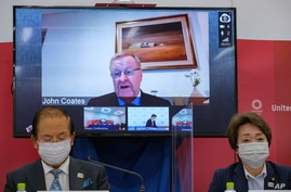 CEO of the Tokyo 2020 Toshiro Muto (L) and President of the Tokyo 2020 Seiko Hashimoto (R) listen to International Olympic Committee vice president John Coates (on screen) delivering a speech during a press conference in Tokyo, Japan, May 21, 2021.