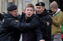 FILE - Police detain journalist Raman Pratasevich in Minsk, Belarus, March 26, 2017. Pratasevich, a founder of a messaging channel popular with the country's opposition, has been arrested after a plane in which he was a passenger was diverted to Minsk.