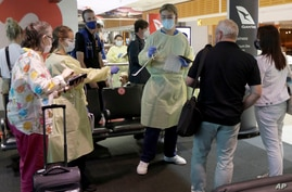 FILE - Arriving passengers are screened by health workers at the airport in Sydney, Australia, Feb. 12, 2021.
