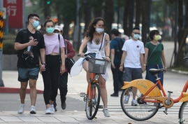 People wear face masks to protect against the coronavirus after authorities raised the COVID-19 alert to level 3 in Taipei, Taiwan, May 15, 2021.
