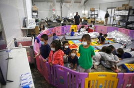 FILE - Unaccompanied migrant children, from ages 3 to 9, watch television inside a playpen at the U.S. Customs and Border Protection facility in the Rio Grande Valley in Donna, Texas, March 30, 2021.