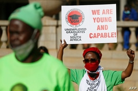 A Unemployed Graduate of South Africa holds a placard and raises her fist while staging a demonstration at Church Square in…