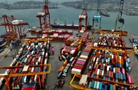 This aerial photograph taken on December 8, 2020 shows shipping containers at the harbour in Keelung. - While the world reels…