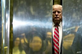 (FILES) In this file photo taken on January 16, 2017 US President-elect Donald Trump boards the elevator after escorting Martin…