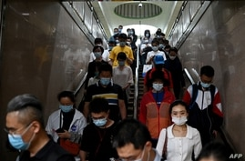This photo taken on June 2, 2021 shows commuters at the subway during rush hour in Beijing. - Ground down by the sapping…