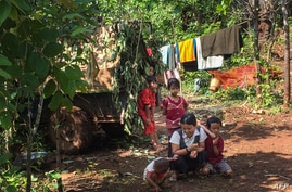 This picture taken on June 3, 2021 shows people taking refuge in a jungle area in Demoso, Kayah state, after they fled from…