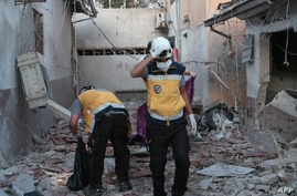 Members of Syria's civil defense service (White Helmets) sift through the rubble at Al-Shifaa hospital following shelling of…