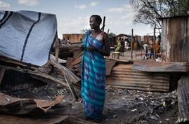 A woman from Murle ethnic group stands at her burnt tea shop in a market in Gumuruk, South Sudan, on June 10, 2021, as her…