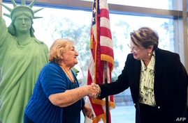 New US citizen Tamam Shanazarian (L) shakes hands with Nancy Alby, field director of USCIS Los Angeles, during a naturalization…