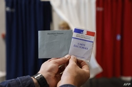 A polling station official holds an electoral card and a ballot at a polling station in Le Touquet, for the second round of the…